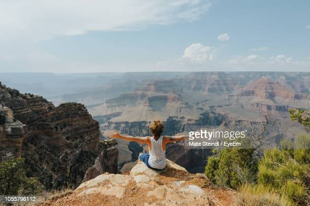 rear view of man with arms outstretched while sitting on rock against sky - category:grand_canyon_national_park stock pictures, royalty-free photos & images