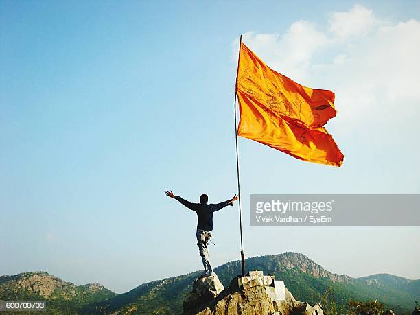 rear view of man with arms outstretched while standing on rocky mountain with flag - flag stock pictures, royalty-free photos & images