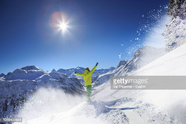 rear view of man with arms raised skiing on snowcapped mountains against clear sky - vorarlberg stock-fotos und bilder