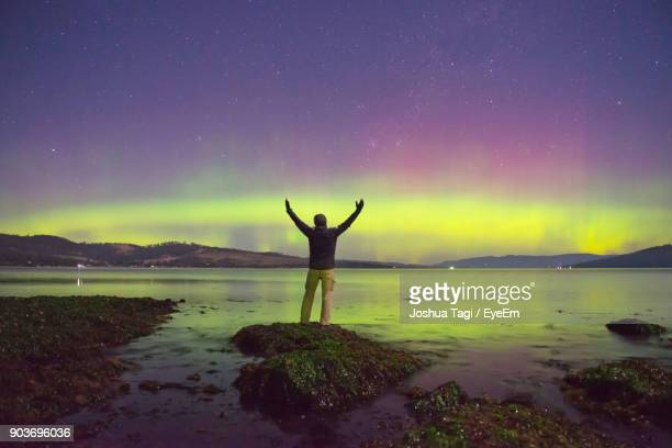 rear view of man with arms raised standing on rock at lakeshore against northern lights at night - hobart tasmania stock pictures, royalty-free photos & images