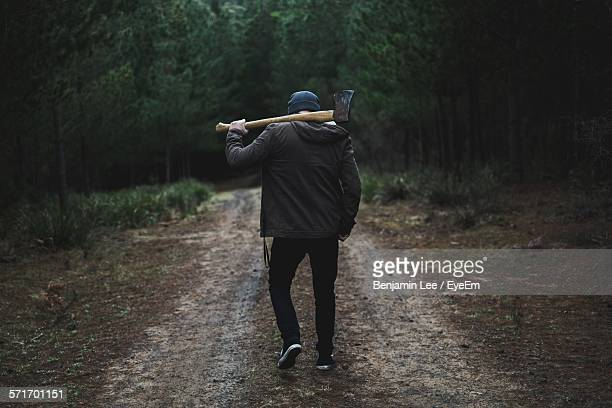 Rear View Of Man With Axe In Forest