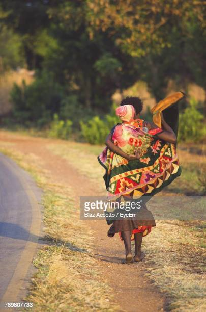 rear view of man with baby walking on road - zambia stock pictures, royalty-free photos & images