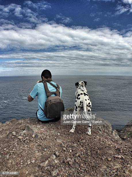 Rear View Of Man With Backpack By Dog Sitting Against Sea And Cloudy Sky