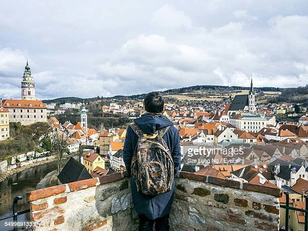 Rear View Of Man With Backpack Looking At Cesky Krumlov Against Cloudy Sky
