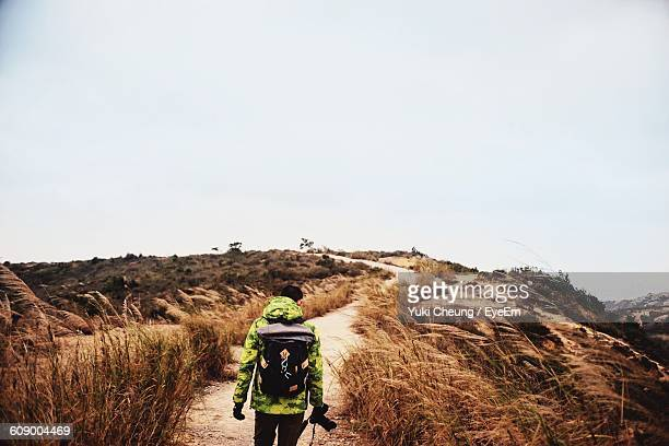 Rear View Of Man With Backpack Walking On Trail At Hill Against Sky