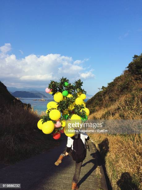 Rear View Of Man With Balloons On Road Against Sky