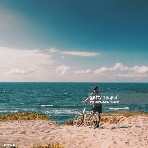 Rear View Of Man With Bicycle Standing At Beach