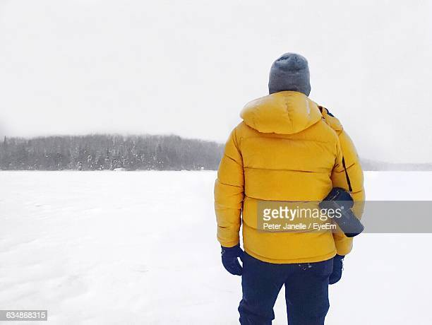 Rear View Of Man With Digital Camera Standing On Snowcapped Field