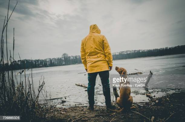 Rear View Of Man With Dog By Lake