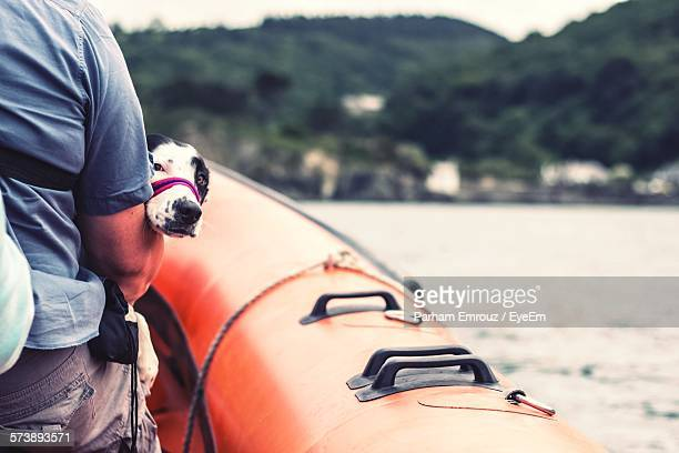 rear view of man with dog on boat sailing in river - parham emrouz stock pictures, royalty-free photos & images