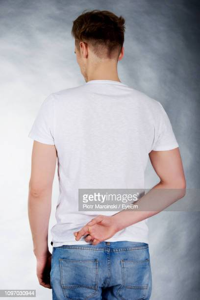 rear view of man with fingers crossed while standing against gray background - hands behind back stock pictures, royalty-free photos & images