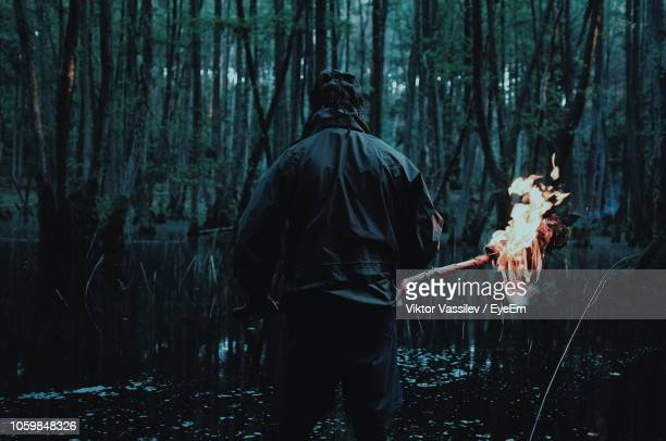 rear view of man with fire standing by trees in forest - survival stock pictures, royalty-free photos & images