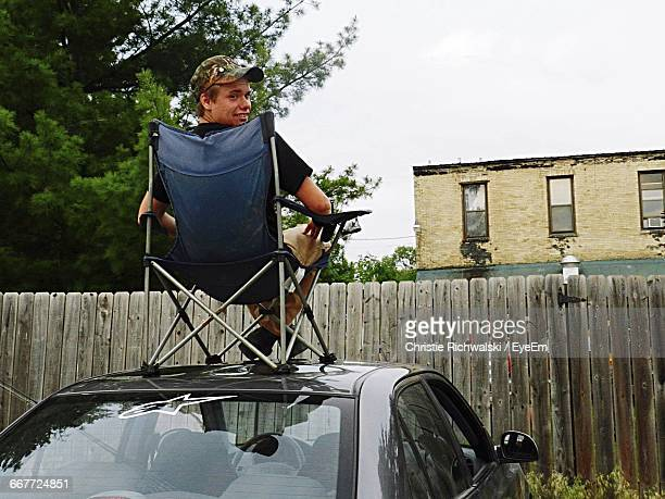 Rear View Of Man With Foldable Chair On Car Roof In Back Yard