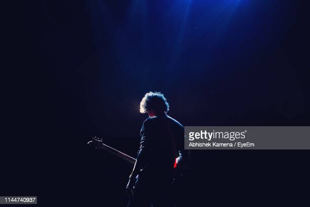 rear view of man with guitar standing in darkroom - chanteur photos et images de collection