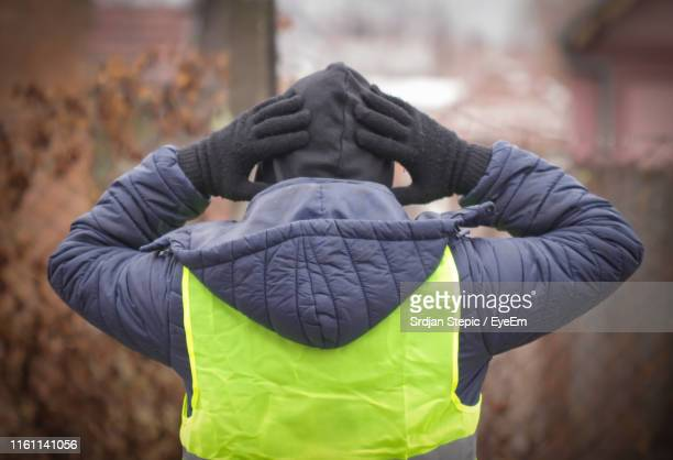 rear view of man with hands behind head wearing warm clothing outdoors - arrest stock pictures, royalty-free photos & images