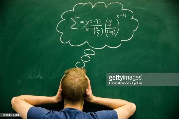 rear view of man with head in hands standing by formula on blackboard - mathematics stock pictures, royalty-free photos & images