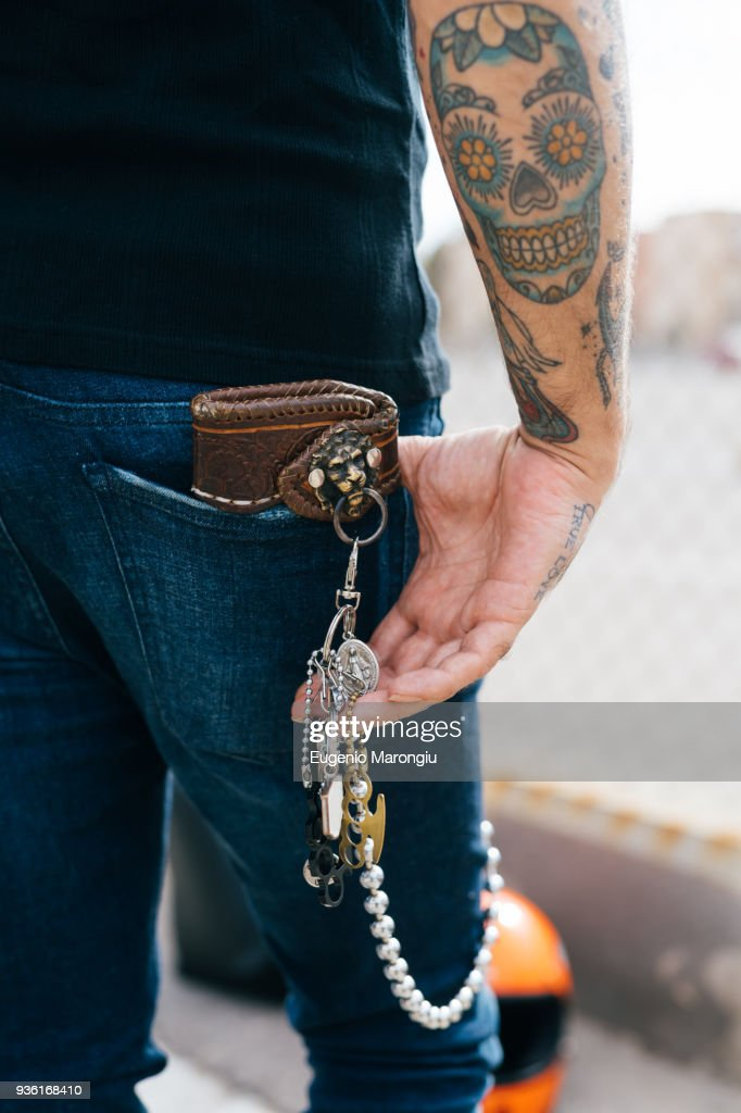 Rear view of man with keys in back pocket and skull tattoo, cropped : Stock Photo