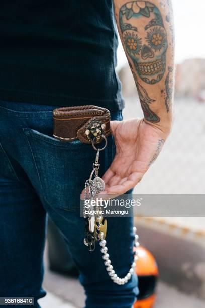 rear view of man with keys in back pocket and skull tattoo, cropped - vaqueros pantalón fotografías e imágenes de stock