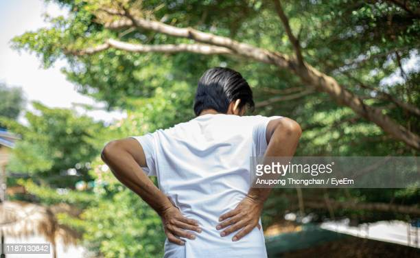 rear view of man with lower back pain standing outdoors - 下背部痛 ストックフォトと画像