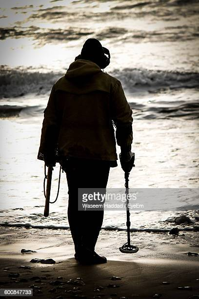 Rear View Of Man With Metal Detector On Shore At Beach