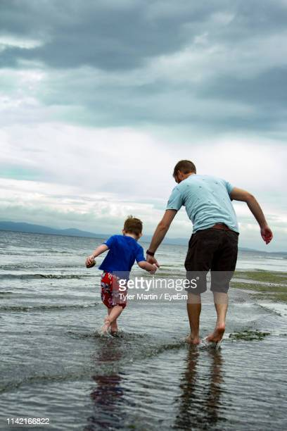 rear view of man with son playing at beach against cloudy sky - pacific ocean stock pictures, royalty-free photos & images