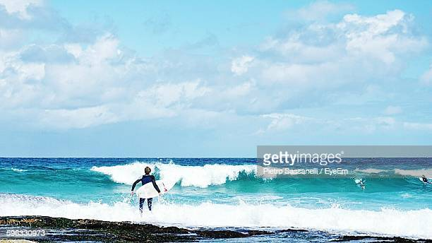 Rear View Of Man With Surfboard Walking Towards Sea Waves Against Cloudy Sky