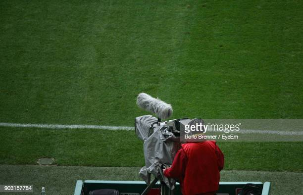 rear view of man with television camera on sports field - photographe professionnel photos et images de collection