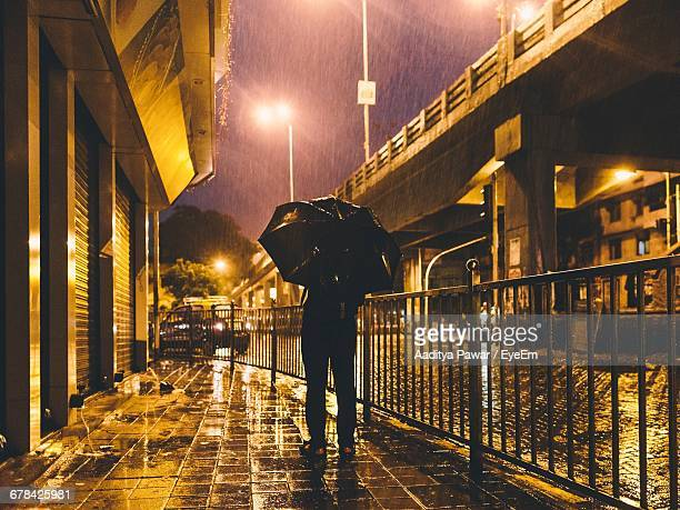 rear view of man with umbrella on footpath at night - maharashtra stock pictures, royalty-free photos & images