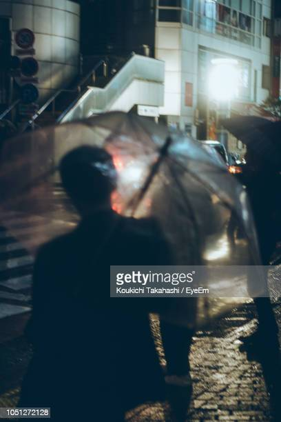 Rear View Of Man With Umbrella On Street At Night