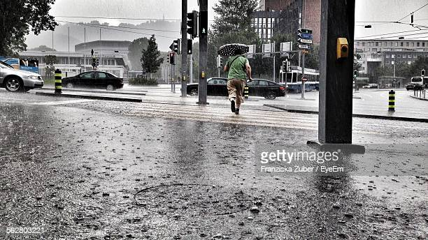 rear view of man with umbrella running towards street - heavy rain stockfoto's en -beelden