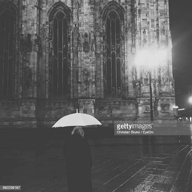 Rear View Of Man With Umbrella Standing By Illuminated Old Cathedral At Night During Monsoon