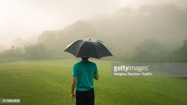 rear view of man with umbrella standing on field against sky - margaux stockfoto's en -beelden
