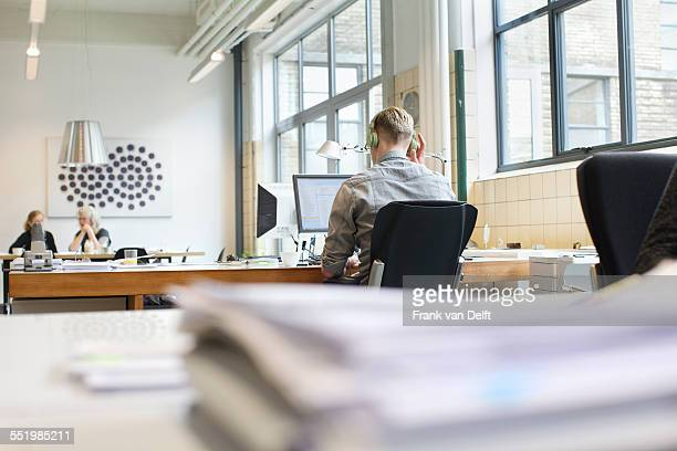 Rear view of man working at desk whilst listening to headphones
