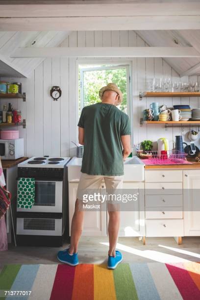 Rear view of man working in kitchen at home