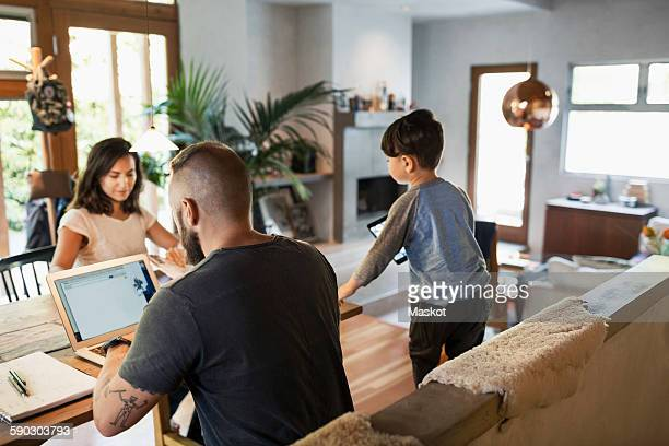 Rear view of man working on laptop while family at dining table in house
