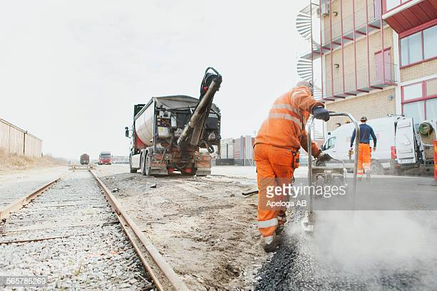 Rear view of manual worker laying asphalt at construction site