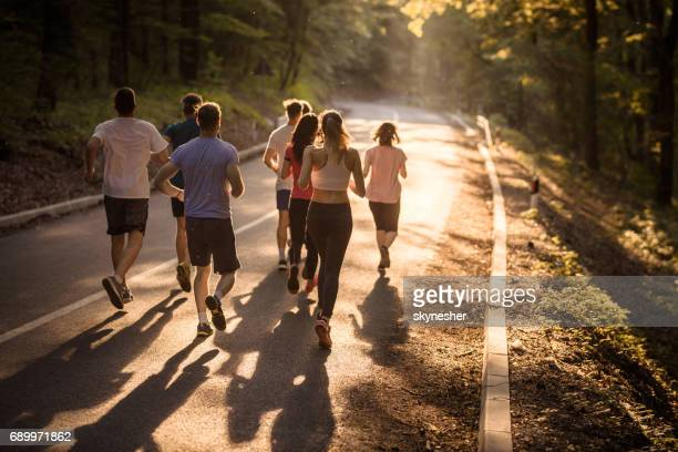 rear view of marathon runners racing at sunset. - organised group stock pictures, royalty-free photos & images