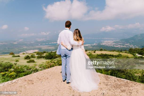 rear view of married couple standing at observation point against sky - newlywed stock pictures, royalty-free photos & images