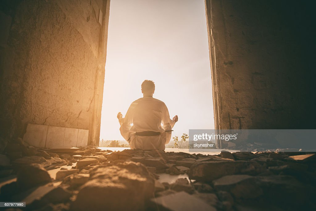 Rear view of martial artist practicing Yoga at sunset. : Stockfoto