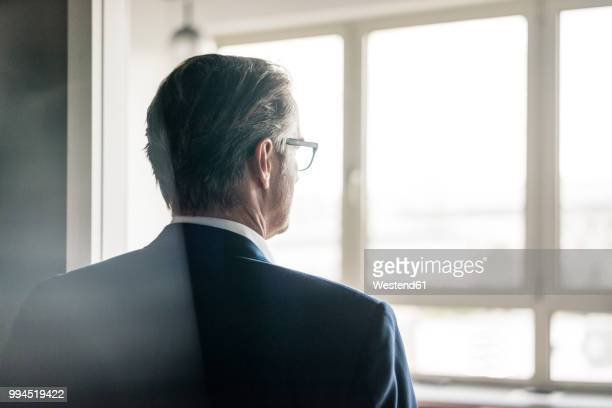 rear view of mature businessman looking out of window - op de rug gezien stockfoto's en -beelden