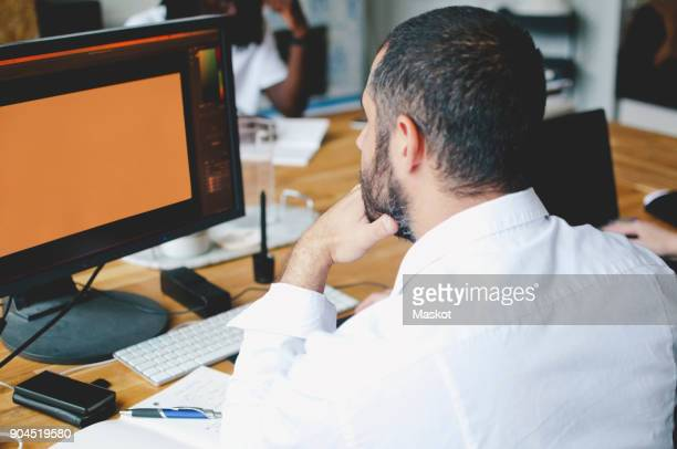 Rear view of mature businessman using computer at table in creative office