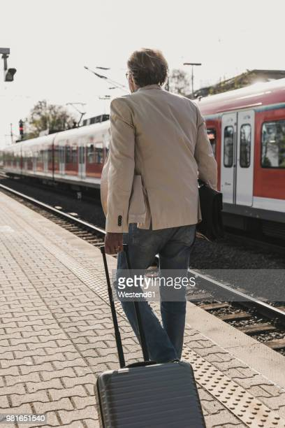 rear view of mature businessman walking at train platform with suitcase - wheeled luggage stock photos and pictures