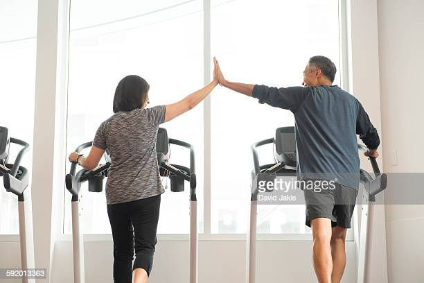 Rear view of mature couple on treadmill doing high five