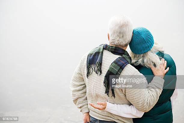 rear view of mature couple - arm around stock pictures, royalty-free photos & images