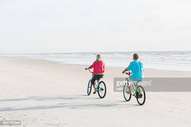 Vista traseira do casal sobre as bicicletas de equitação praia