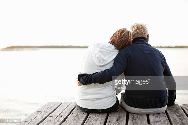 rear view of mature couple sitting on pier looking at lake - heteroseksueel koppel stockfoto's en -beelden