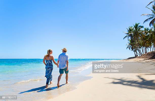 Rear view of mature couple strolling along beach, Dominican Republic, The Caribbean