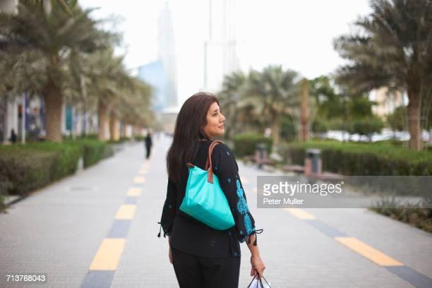 Rear view of mature female shopper carrying shopping bags, Dubai, United Arab Emirates