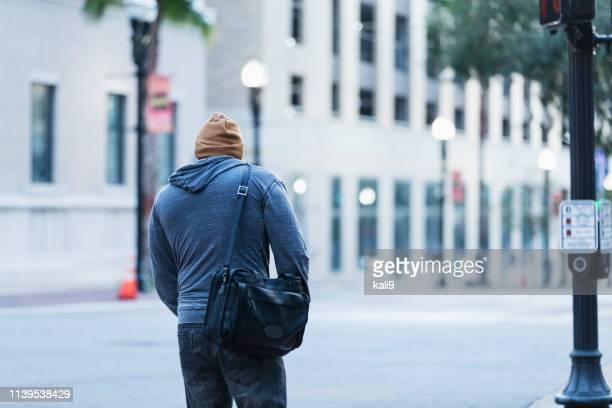 achteraanzicht van volwassen hispanic man wandelen in de stad - onherkenbaar persoon stockfoto's en -beelden