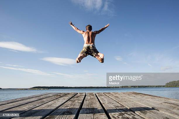 rear view of mature man diving into sea - jetty stock pictures, royalty-free photos & images